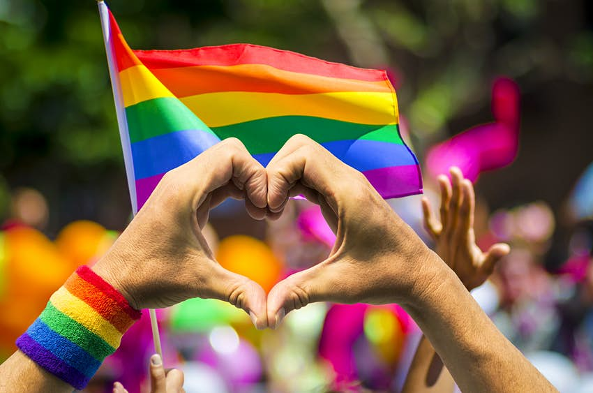 Pride in the US: a pair of hands create a heart symbol, backdropped by rainbow flags © lazyllama / Shutterstock