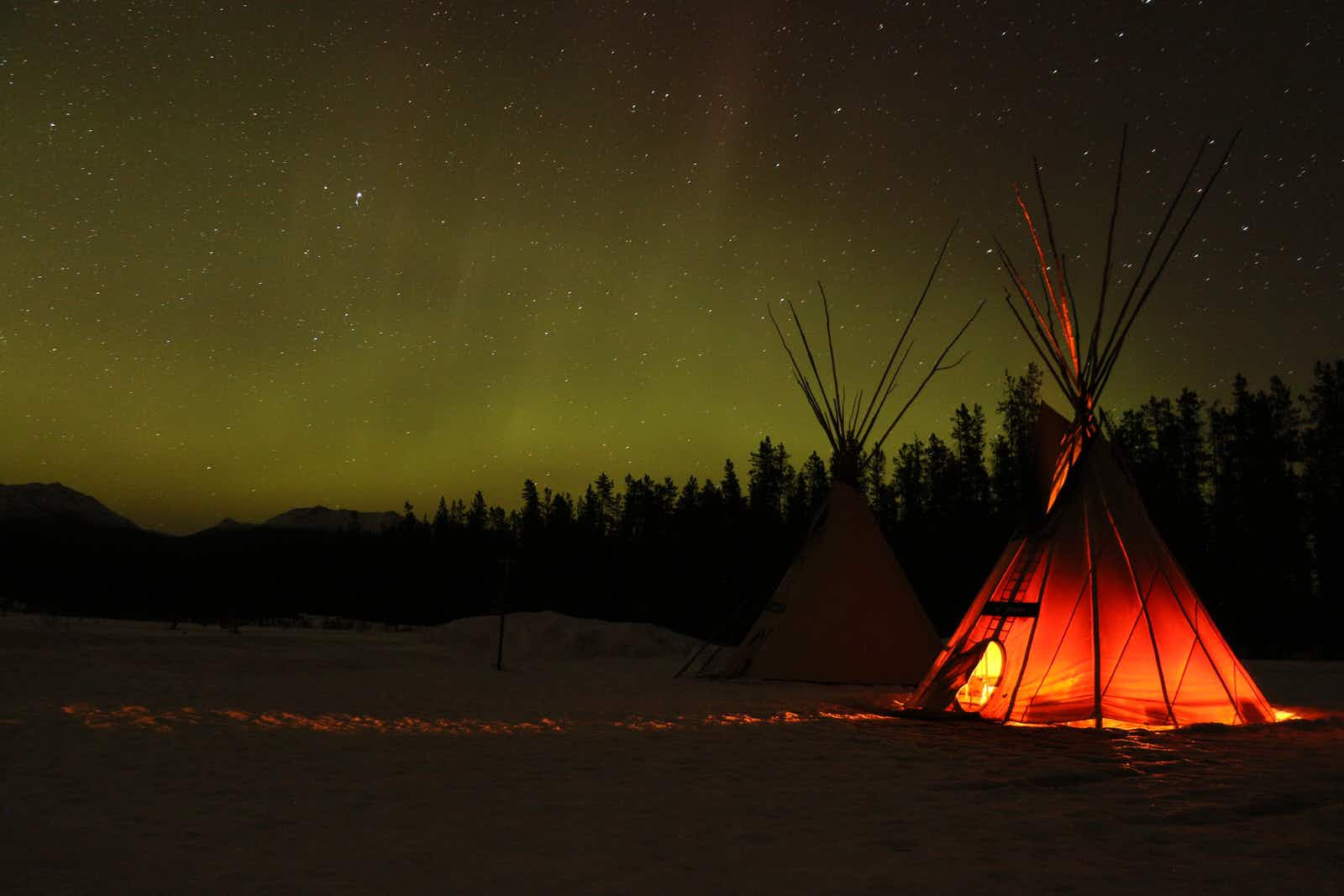 The northern lights glow in the distance on a black landscape while a tipi glows in the foreground © Mike MacEacheran / Lonely Planet