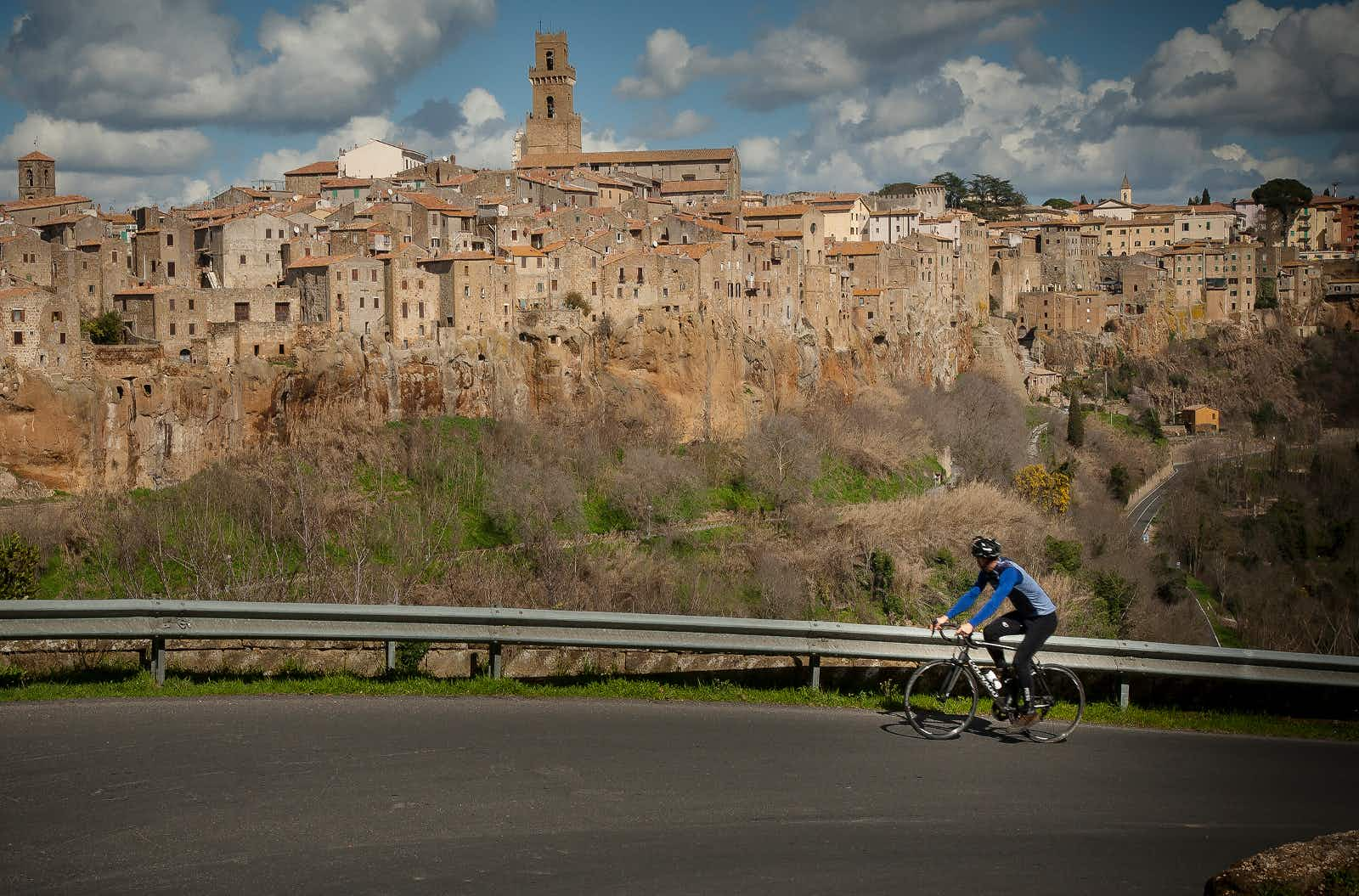 A cyclist climbing up a steep road, with his head turned away from the camera and towards the impressive medieval skyline of Pitigliano © Ciclica & Foto Mariollorca.com
