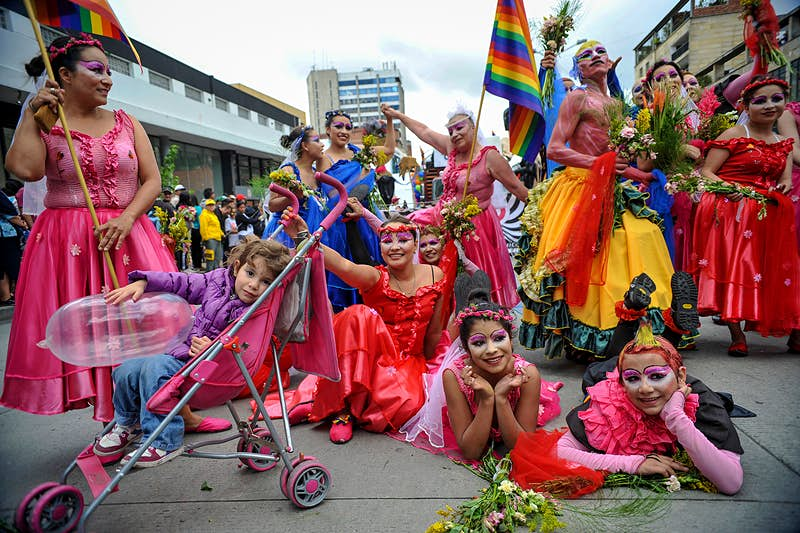 A group of people dressed in pink and red dresses hold Pride flags in Bogotá © GUILLERMO LEGARIA / GettyImages