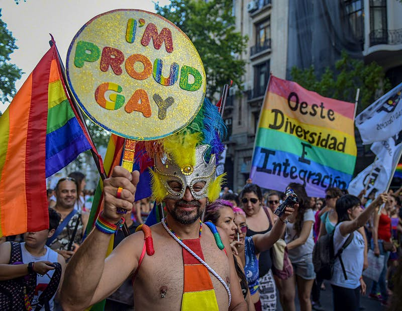 "A shirtless man wears a masquerade mask and holds a sign that says ""I'm Proud Gay""© JUAN MABROMATA / Getty Images"