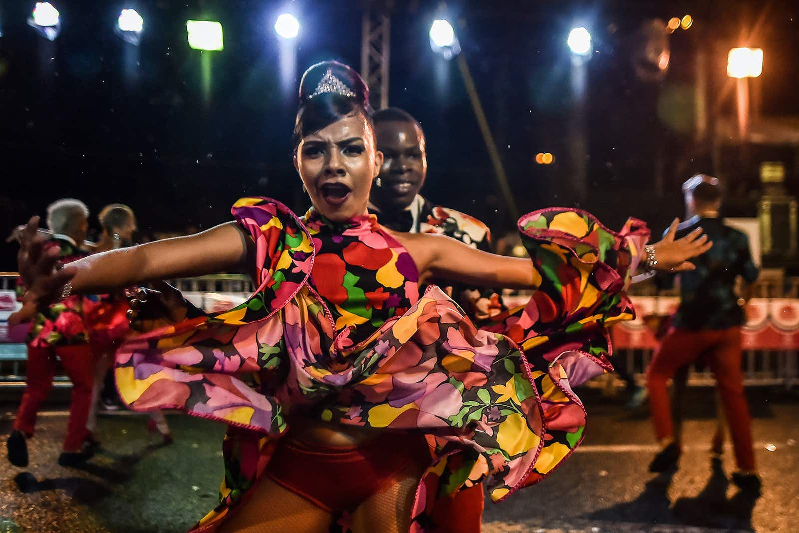 "Colombian salsa dancers perform during the ""Salsodromo"" parade during the opening of the 60th Cali Fair in Cali on December 25, 2017. More than 1,500 dancers from different salsa schools in the city danced on the streets wearing colorful costumes, representing all aspects of salsa music culture in the largest parade of salsa dancers in the world. / AFP PHOTO / Luis ROBAYO        (Photo credit should read LUIS ROBAYO/AFP/Getty Images)"