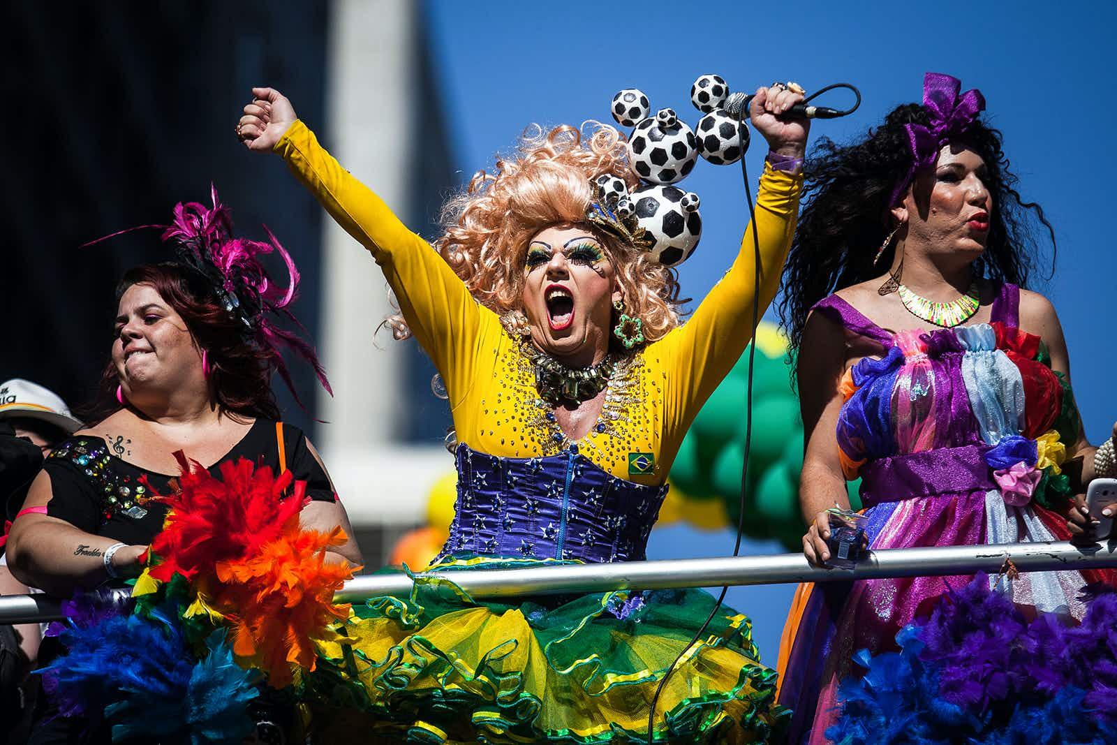Three brightly clothed individuals celebrate Pride in Sao Paulo