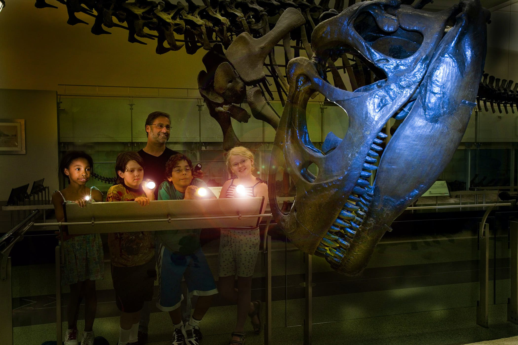 Four kids and an adult study a T. Rex skeleton with flashlights © AMNH/D. Finnin