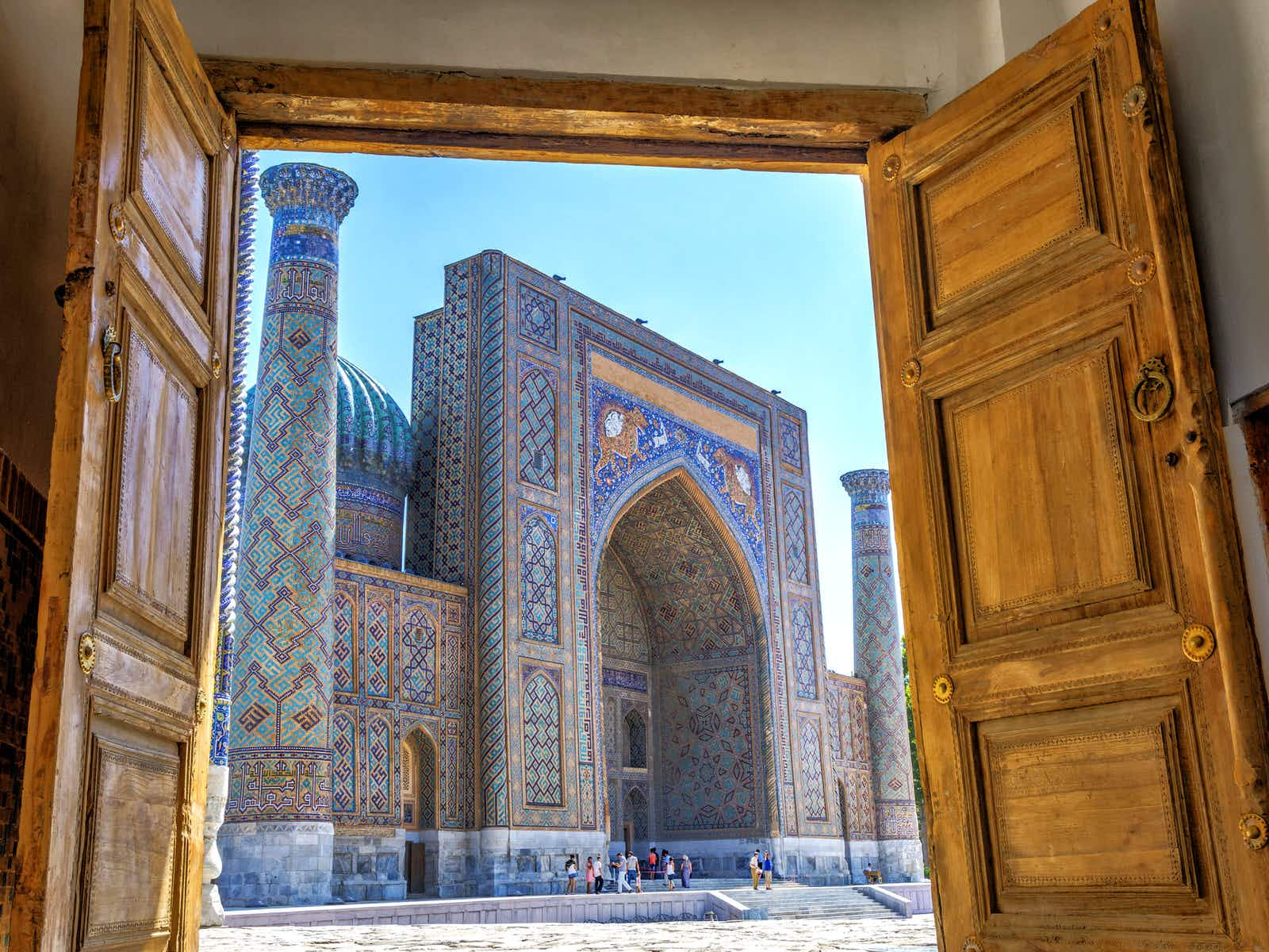 Wooden doors open onto a sunny blue-tiled Islamic square. Uzbekistan's new policies are making it easier to visit its stunning monuments, such as the Registan © Dinozzzaver / Shutterstock