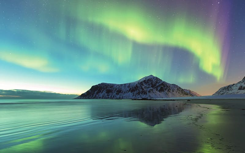 Green waves of the aurora move over a beach in Norway. A snowy mountain is in the background. © Spreephoto.de / Getty Images