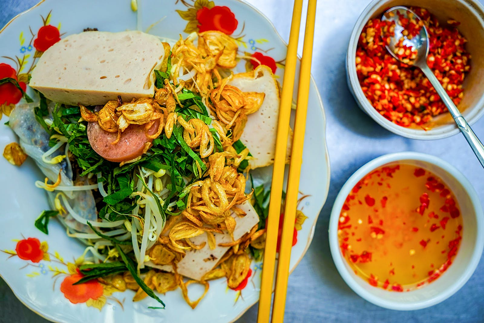 A close-up of a bowl of bánh cuốn, with two small bowls of orange sauces © James Pham / Lonely Planet