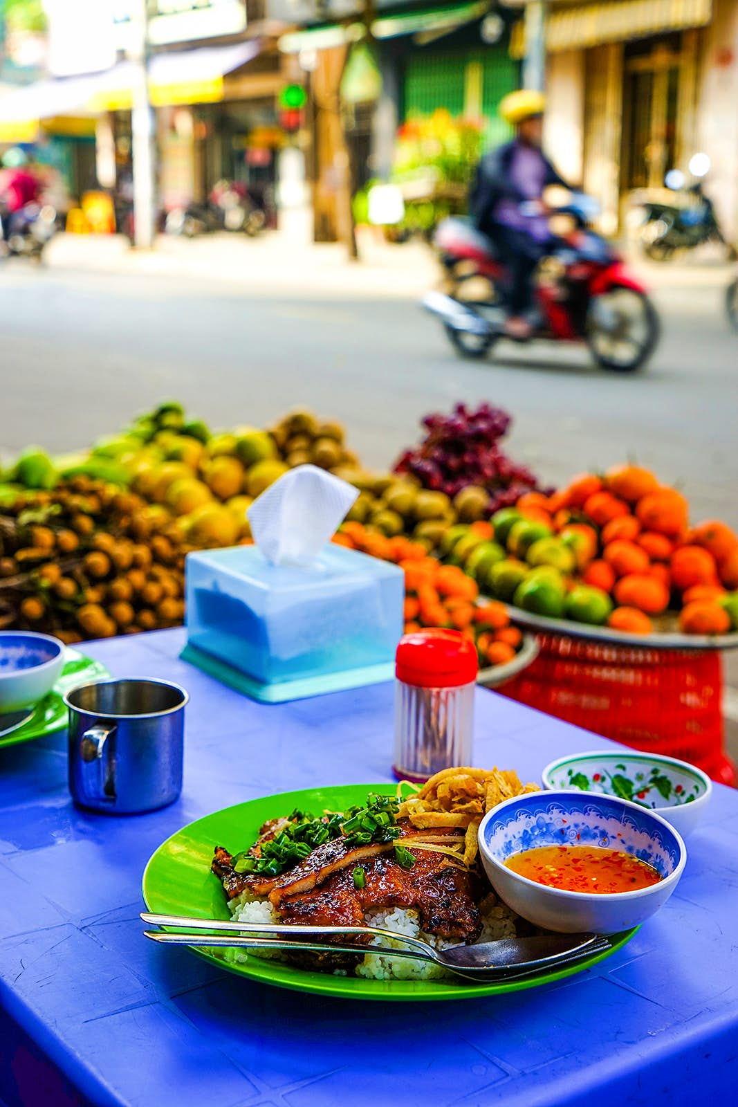 A bowl of food on a blue tablecloth in the foreground with fruit and a man on a motorbike in the background © James Pham / Lonely Planet