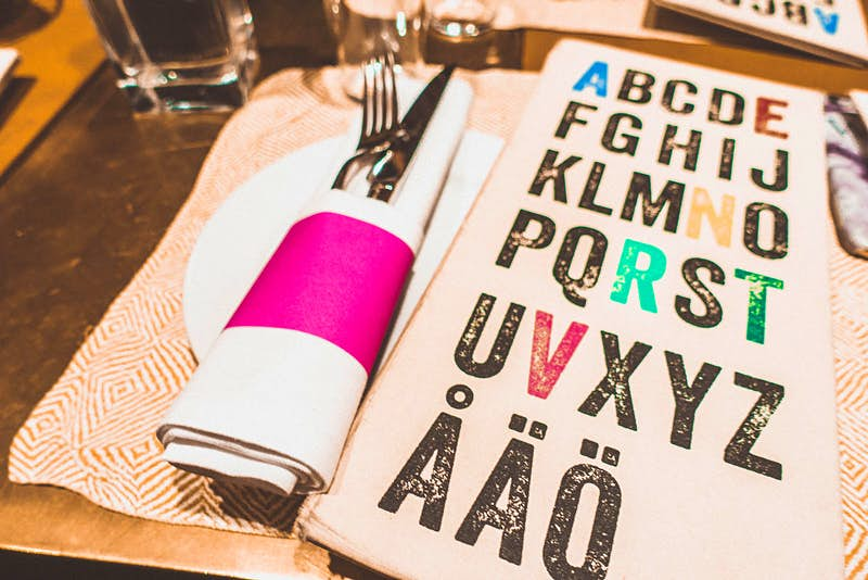 The colourful place settings at Taverna Brillo restaurant with a white and pink napkin and a stylish menu © Megan & Whitney Bacon-Evans / Lonely Planet