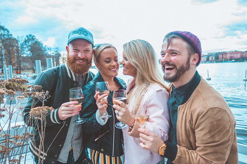 LGBT friends laughing and enjoying a glass of wine at floating bar Mälarpaviljongen © Megan & Whitney Bacon-Evans / Lonely Planet