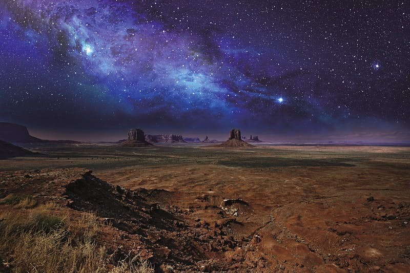 Stars and the milky way stretch over the rock towers of Monument Valley © Claudio Ventrella / Getty Images