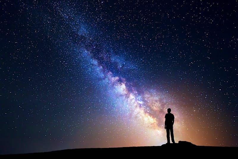 A person stands on a rock, backlit by the Milky Way © Denis Belitsky / Shutterstock