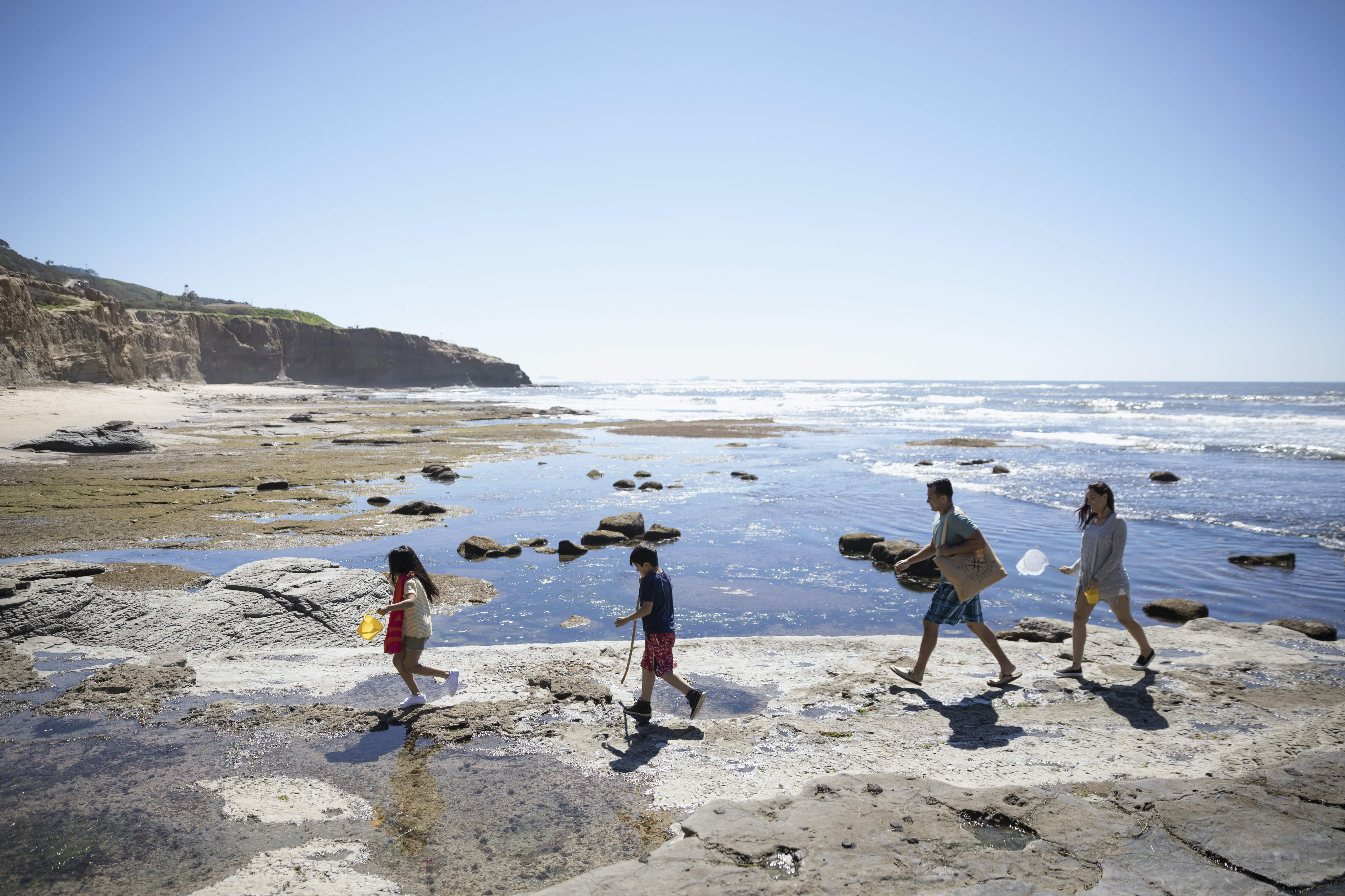Family of four makes their way down to the beach © Hero Images / Getty Images