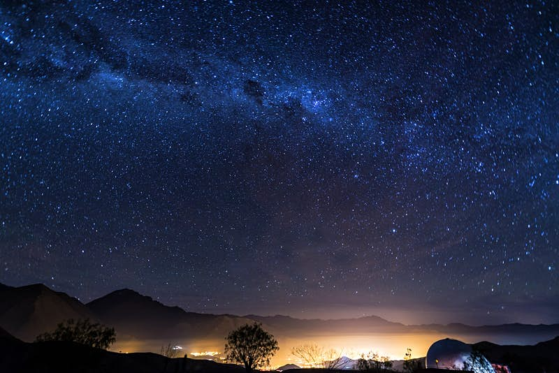 Stars of the Milky Way stretch over the Elqui Valley in Chile. Lights from a town shine below. ©DC_Colombia/Getty Images