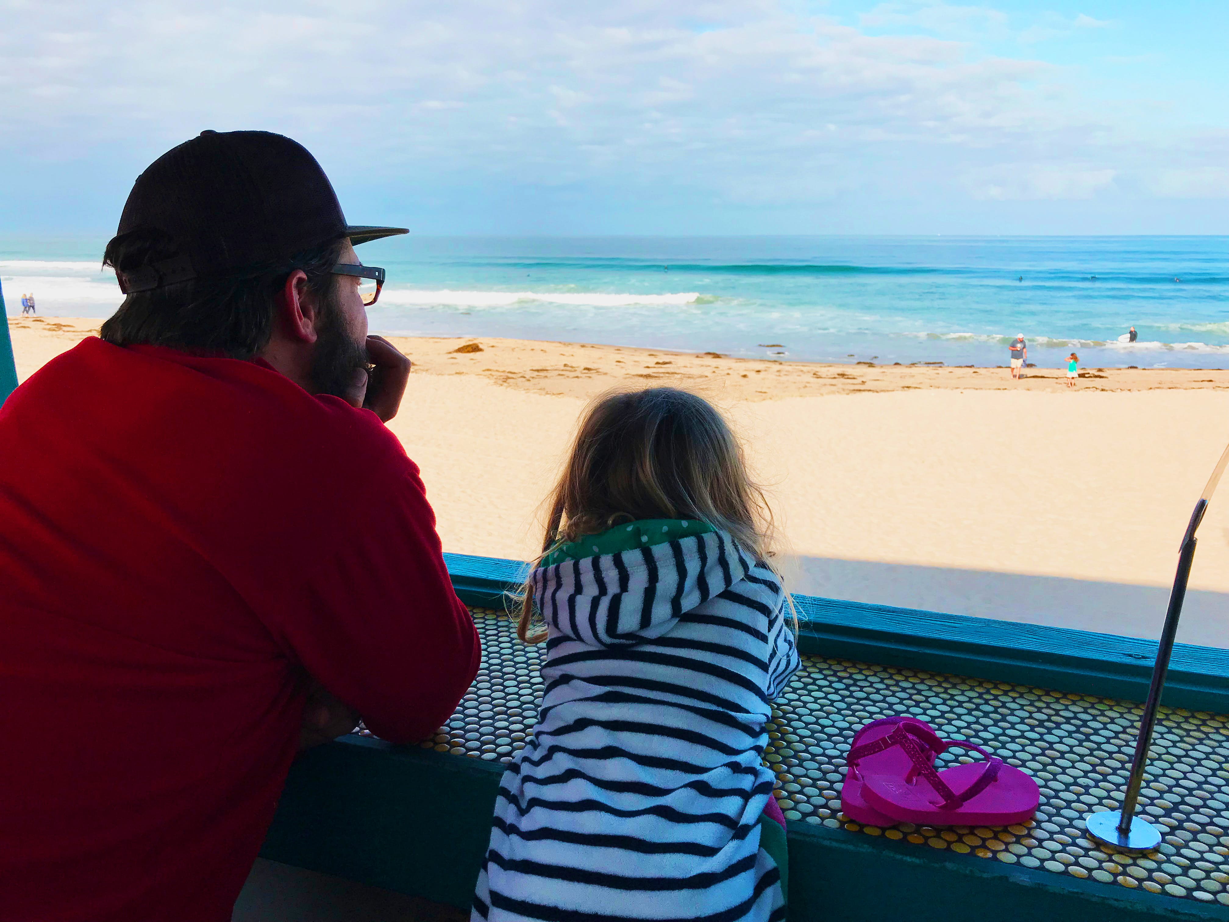 A man and his daughter watch surfers on the beach while waiting for food © Sarah Stocking / Lonely Planet