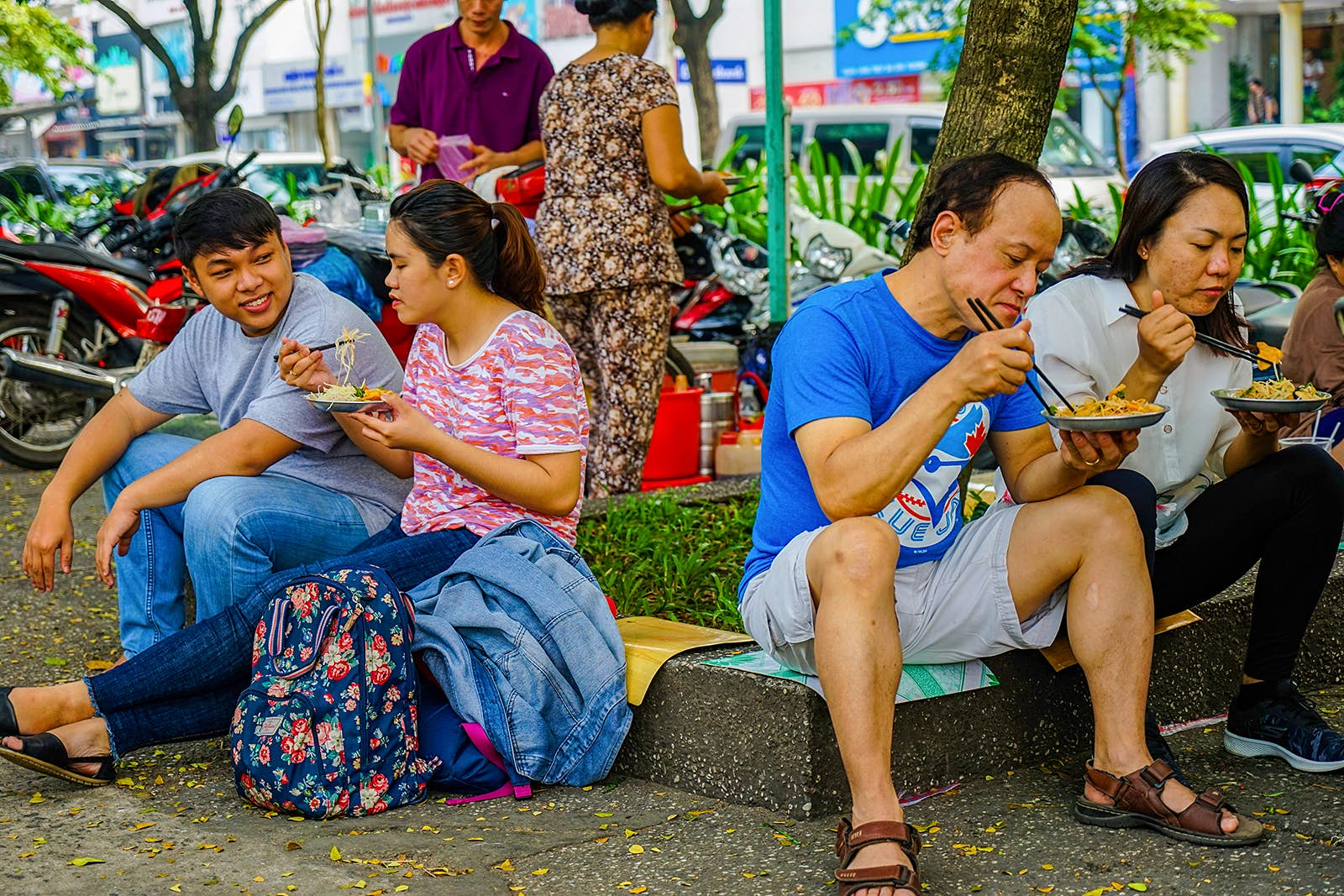 People sit on a curb eating plates of papaya salad © James Pham / Lonely Planet