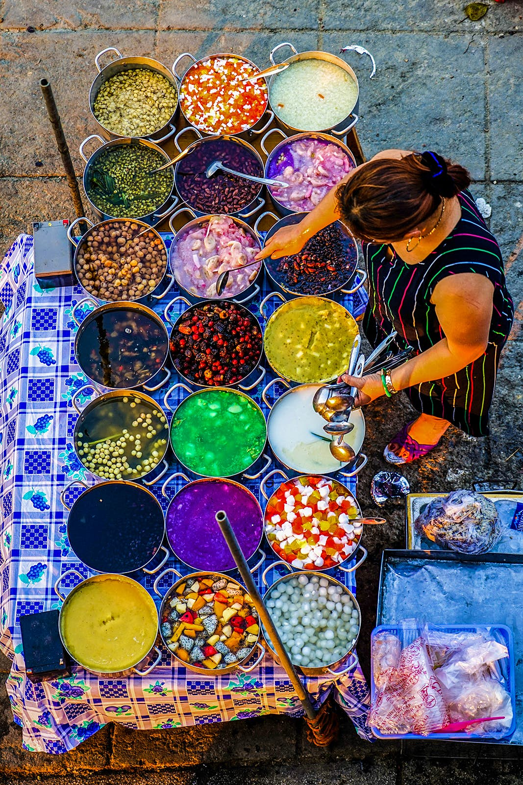 A woman tends to several pots filled with different-colored sweets © James Pham / Lonely Planet