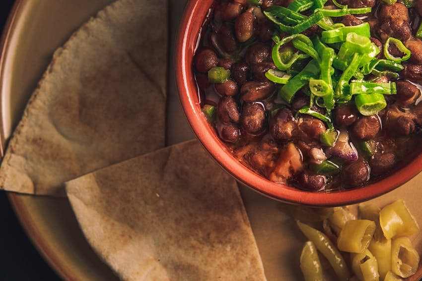 Fuul, fava beans with vegetables and pita bread, often eaten for breakfast in Egypt © Adamsgraphy / Shutterstock