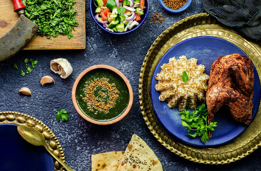 Egyptian dish of molokhiyya placed with rice, chicken, pita bread and green salad © Dina Saeed / Shutterstock