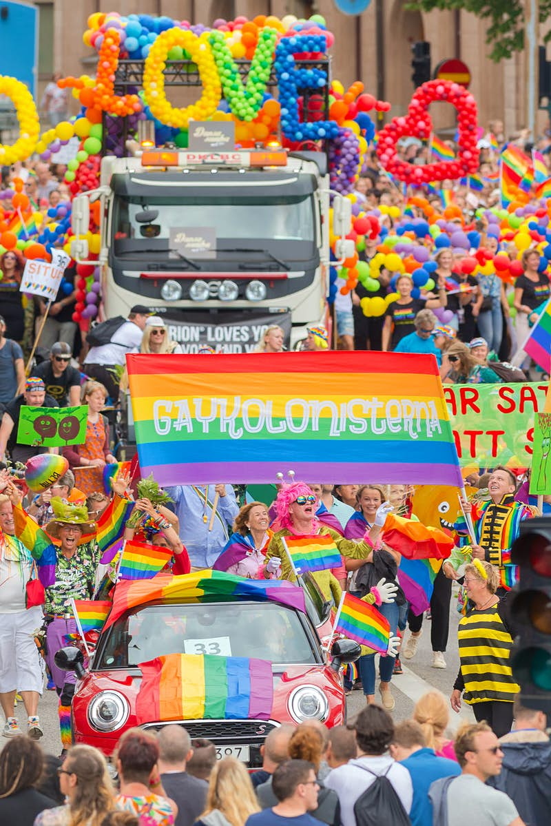 Truck with balloons spelling 'love', surrounded by crowds of marchers, at the Stockholm Pride Parade in 2017 © Stefan Holm / Shutterstock