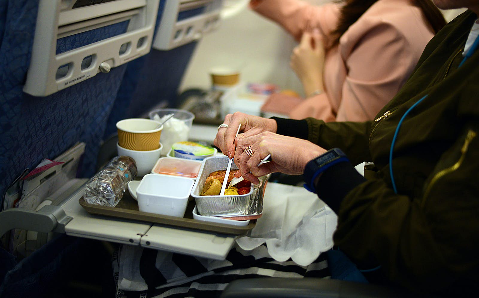 A woman eating an in-flight meal on a plane © Cheryl Chan / Getty Images