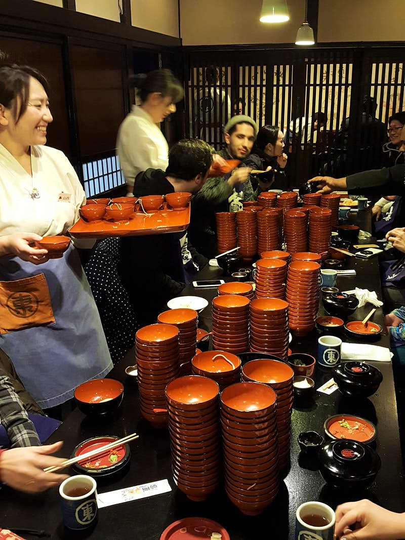 The busy interior of Azumaya, Morioka with long table full of stacks of small empty noodle bowls and customers, as staff stand beside with trays of more noodles