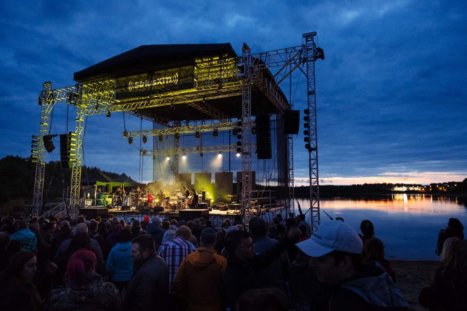 A large outdoor, open-air stage is lit at twilight as it sits beside a lake, while music fans listen © Festival de musique émergente