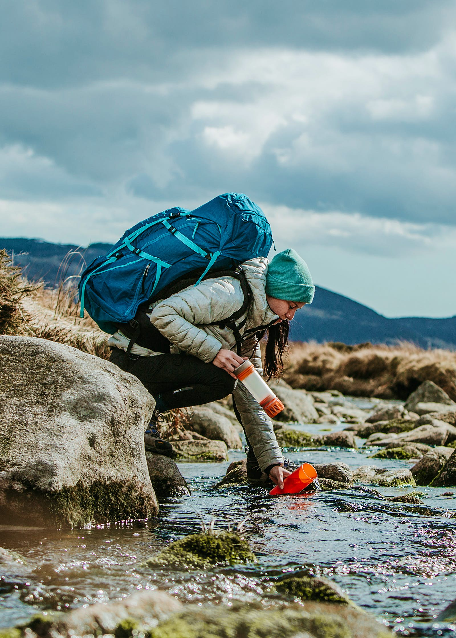 A female hiker filling her GRAYL bottle in a stream © GRAYL
