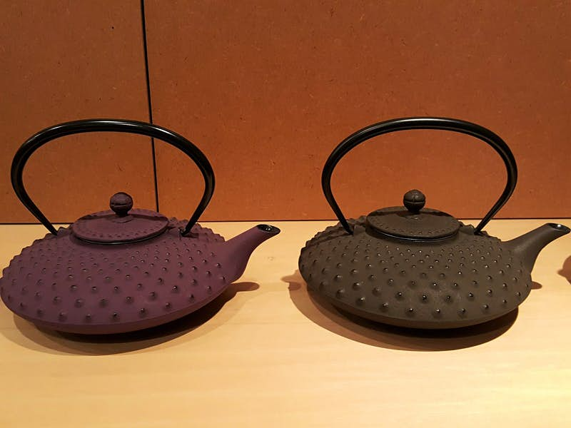 Two cast-iron tea kettles, one purple and one black, on a display shelf at Iwachu