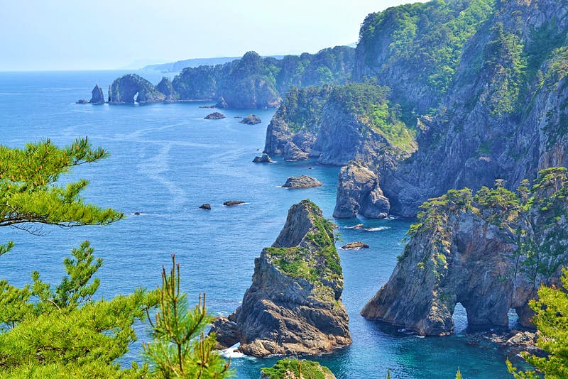 View of the rocky coastline of the Kitayamazaki Cliffs in Iwate on a clear and sunny day. The sheer, rocky cliffs are topped with bright green grass and surrounded by restless sea.