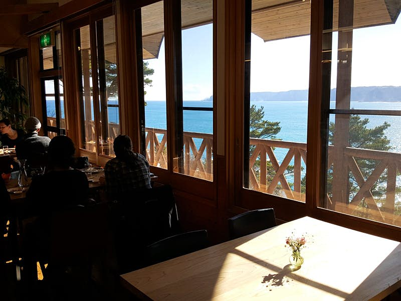 View from inside a restaurant looking through large windows to the blue ocean and cliffs beyond