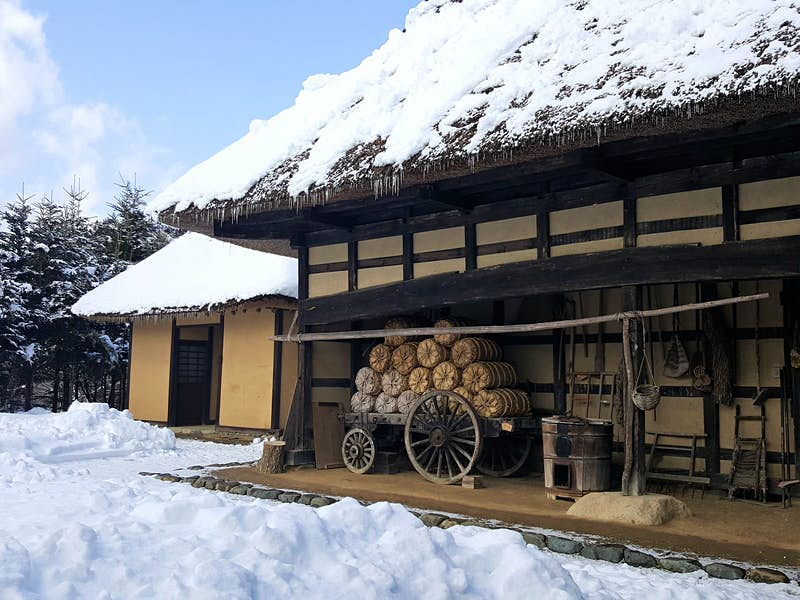 An old thatched-roof farmhouse with snow on the roof and on the ground outside, at Tono Furusato Village