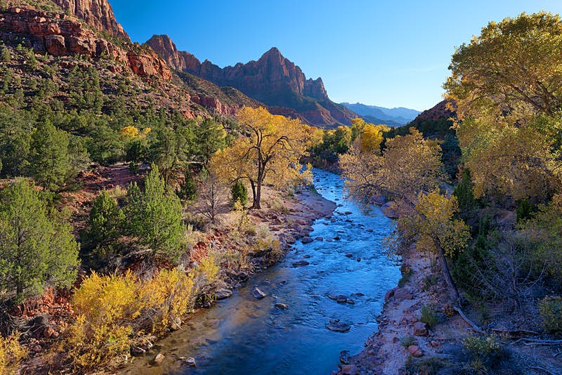 A river flows through the National Park, with yellow and green trees contrasting the red rocky outcrops