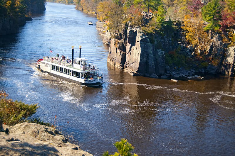 A paddle boat on the St. Croix River. Trees on the rocky riverbanks have leaves of red, orange, gold and green
