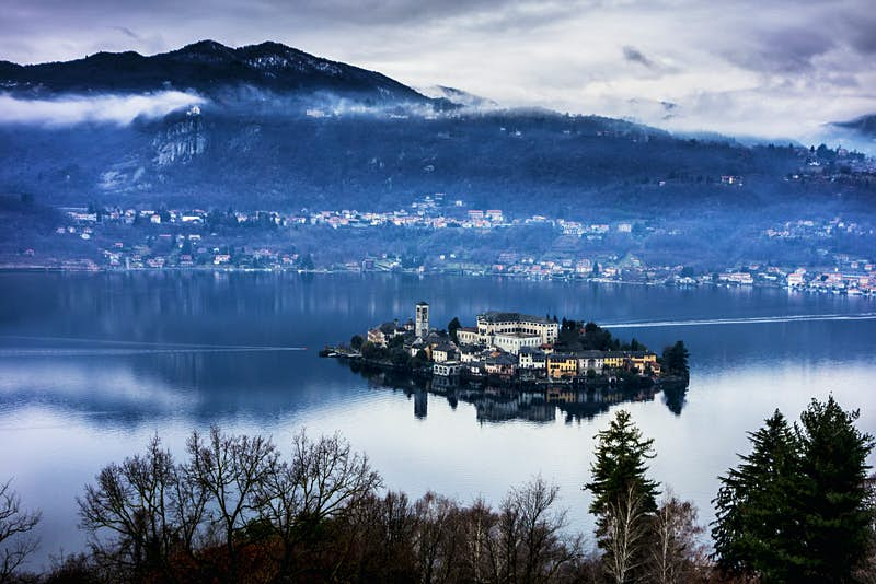 Isola San Giulio, packed with historic buildings, sits in the middle of Lake Orta, with mountains rising behind © Francesco Meroni / Getty Images