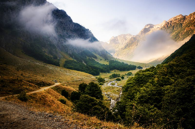 A rugged valley, wreathed with clouds and flanked by craggy mountains © Cristiano Alessandro / Getty Images