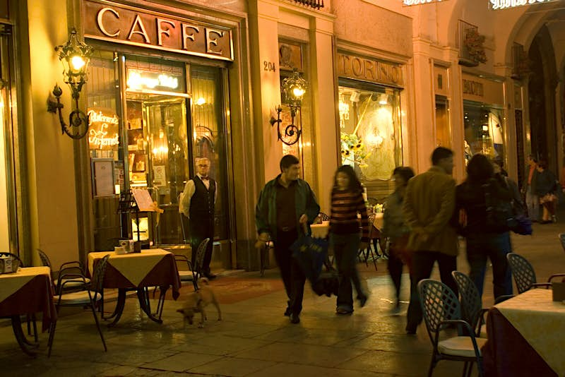 People walk past the Belle Epoque facade of Caffè Torino at night © Bob Sacha / Getty Images
