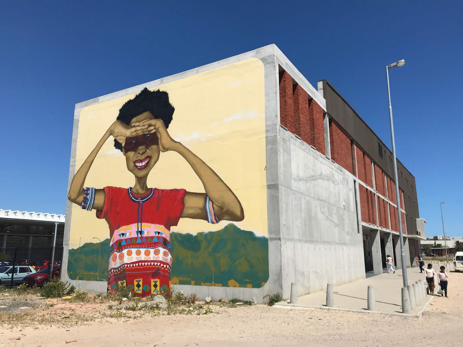 A massive mural of young black South African woman, with her arms raised to shade her eyes from the sun, stares out from the end of the Isivivana Centre's concrete facade © Simon Richmond / Lonely Planet