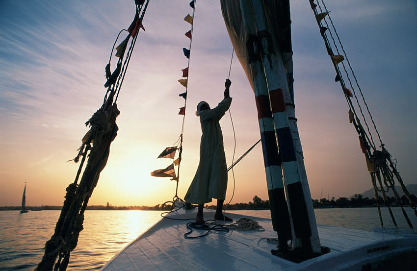 Egypt, Aswan, man sailing felucca on the River Nile at sunset © Nicholas Pitt / Getty Images
