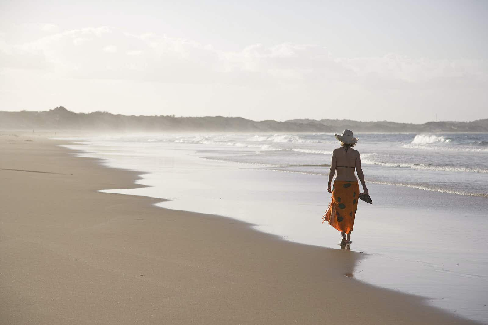 A women wearing a brimmed straw hat, sarong wrap and bikini top walks away from the camera along the wave strewn beach at Tofo © Julian Love / Getty Images