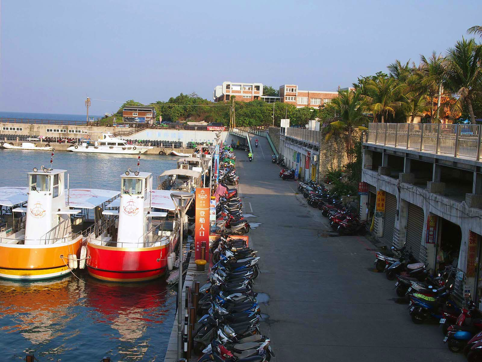 A view of the harbour with docked boats and scooters parked along the waterside. It's easy to hire scooters to get around Little Liuchiu © Tess Humphrys / Lonely Planet