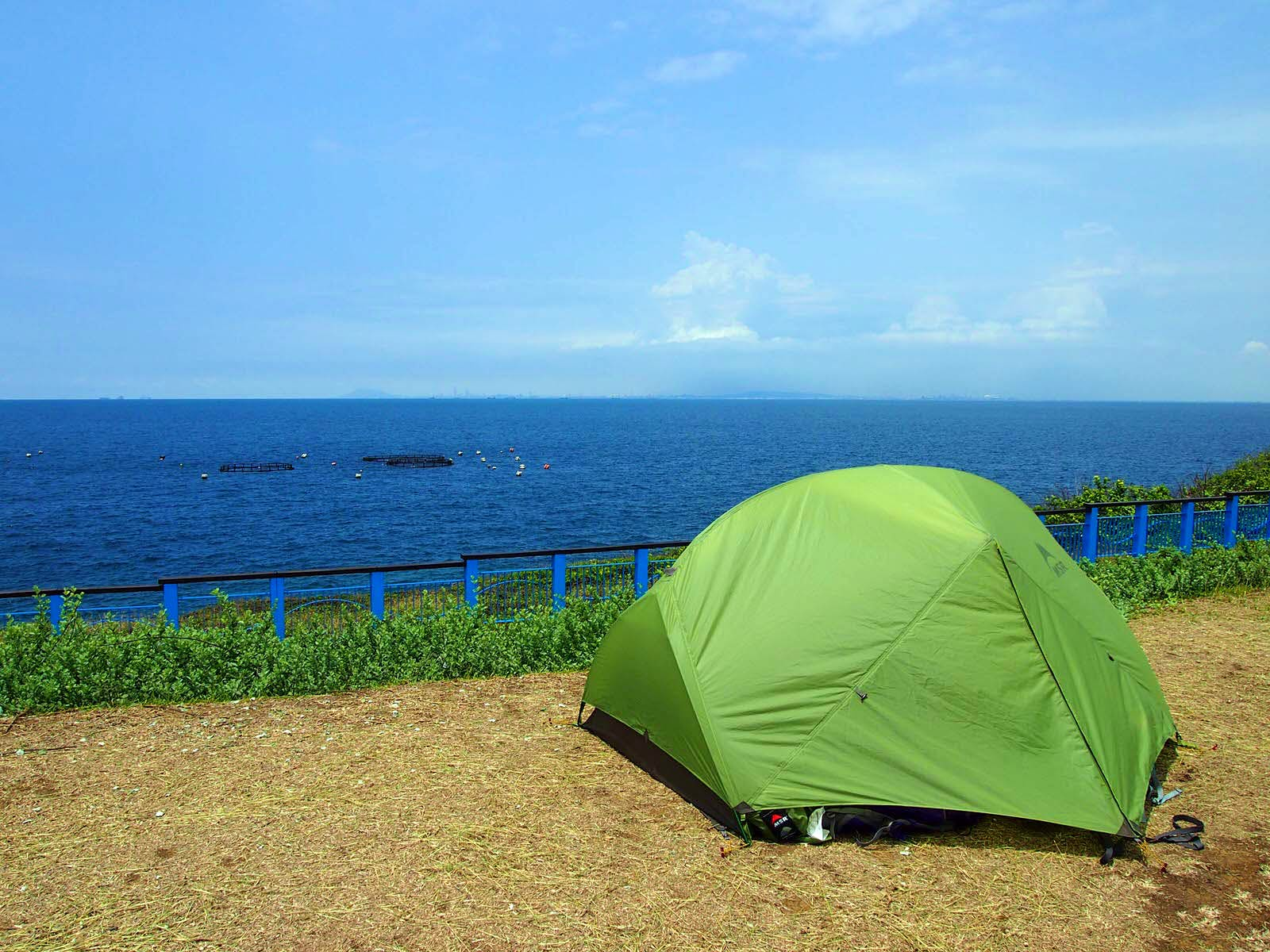 A green tent pitched on a patch of dirt overlooking the sea. Camping is popular on Little Liuchiu and offers amazing views © Tess Humphrys / Lonely Planet