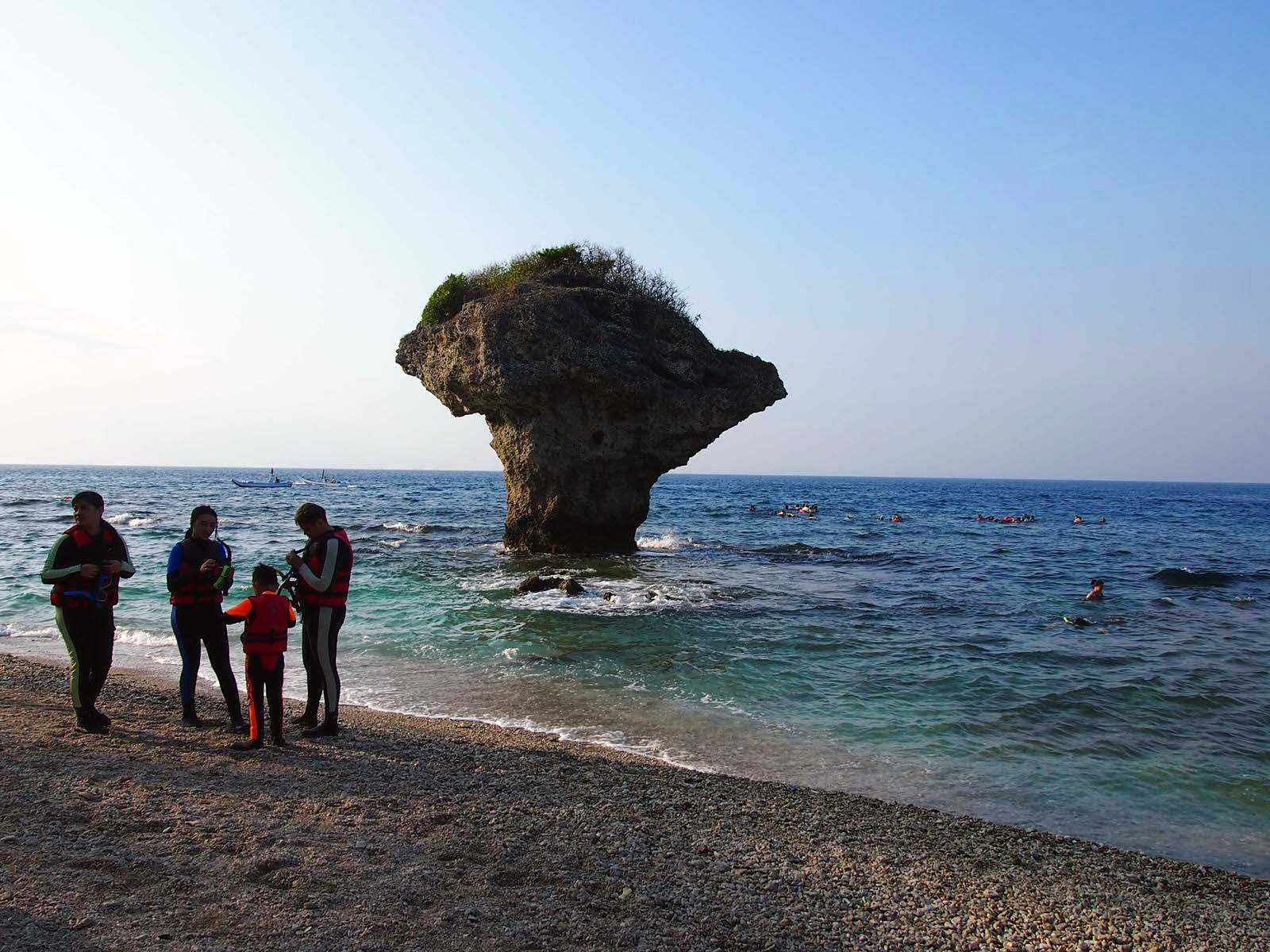 A family prepares to go snorkelling on the beach in front of Vase Rock. The waters around Vase Rock are the most popular place for snorkelling © Tess Humphrys / Lonely Planet