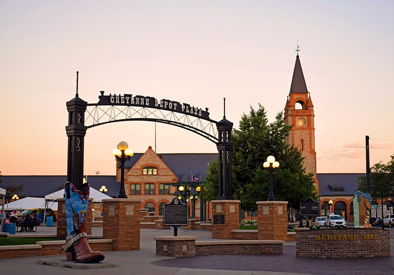 Buildings and a plaza glow in the warmth of a sunset, with a train-shaped sign and oversized cowboy-boot sculpture in Cheyenne, Wyoming © Dave Parfitt / Lonely Planet