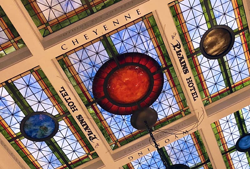 The words 'Cheyenne', 'Wyoming' and 'The Plains Hotel' surround a rectangular stained glass ceiling, with blue and red panes of glass and a circle motif © Dave Parfitt / Lonely Planet