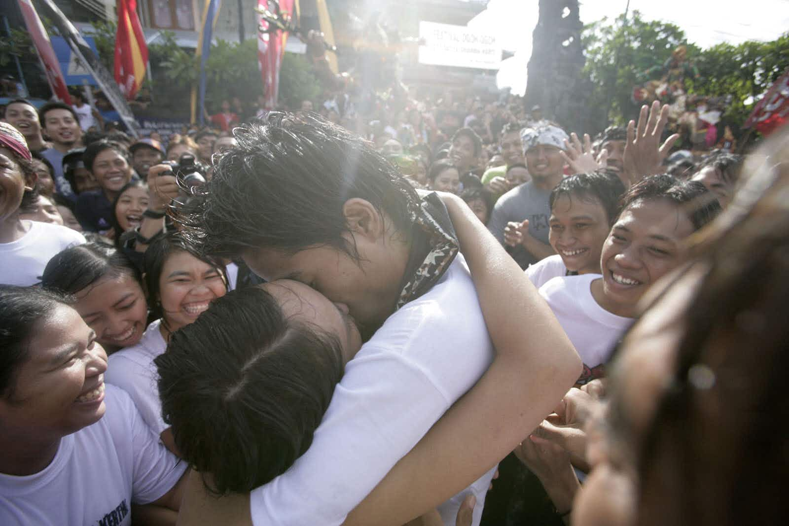 """DENPASAR, INDONESIA - MARCH 20:  A young Balinese couple kiss during the Kissing Festival held in Sesetan village on March 20, 2007 near Denpasar, Bali, Indonesia. This annual Kissing Festival is held just one day after Balinese Hindus celebrate the Nyepi Day or Silence Day. The Kissing Festival known locally as """"Med-Medan"""", allows male and female teenagers to kiss each other in public. The kissing begins after first praying in the """"Banjar"""" or village temple and is used to help protect the village from bad luck. While the festival has attracted outsiders, the only people permitted to participate are the local Banjar Kaja Sesetan villagers. (Photo by Dimas Ardian/Getty Images)"""