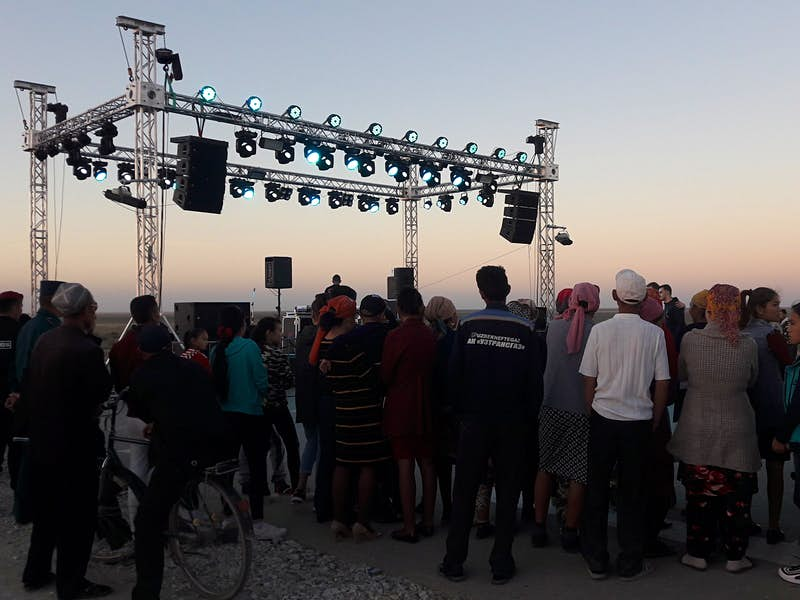 Festival attendees stand near a stage erected in the desert as the sun sets.