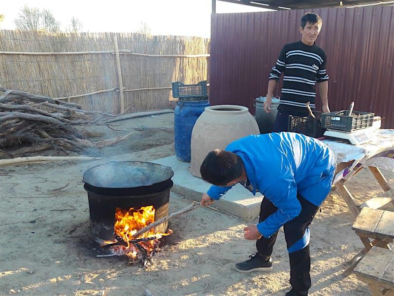One man putting a stick into a fire under a large pot