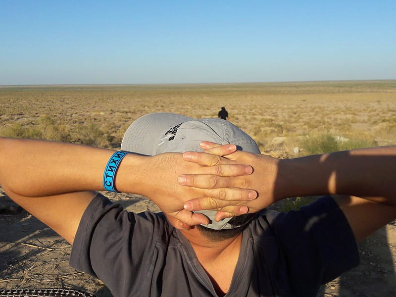 A man with his hands crossed behind his head is seen from behind, with the desert of the former Aral Sea in front of him