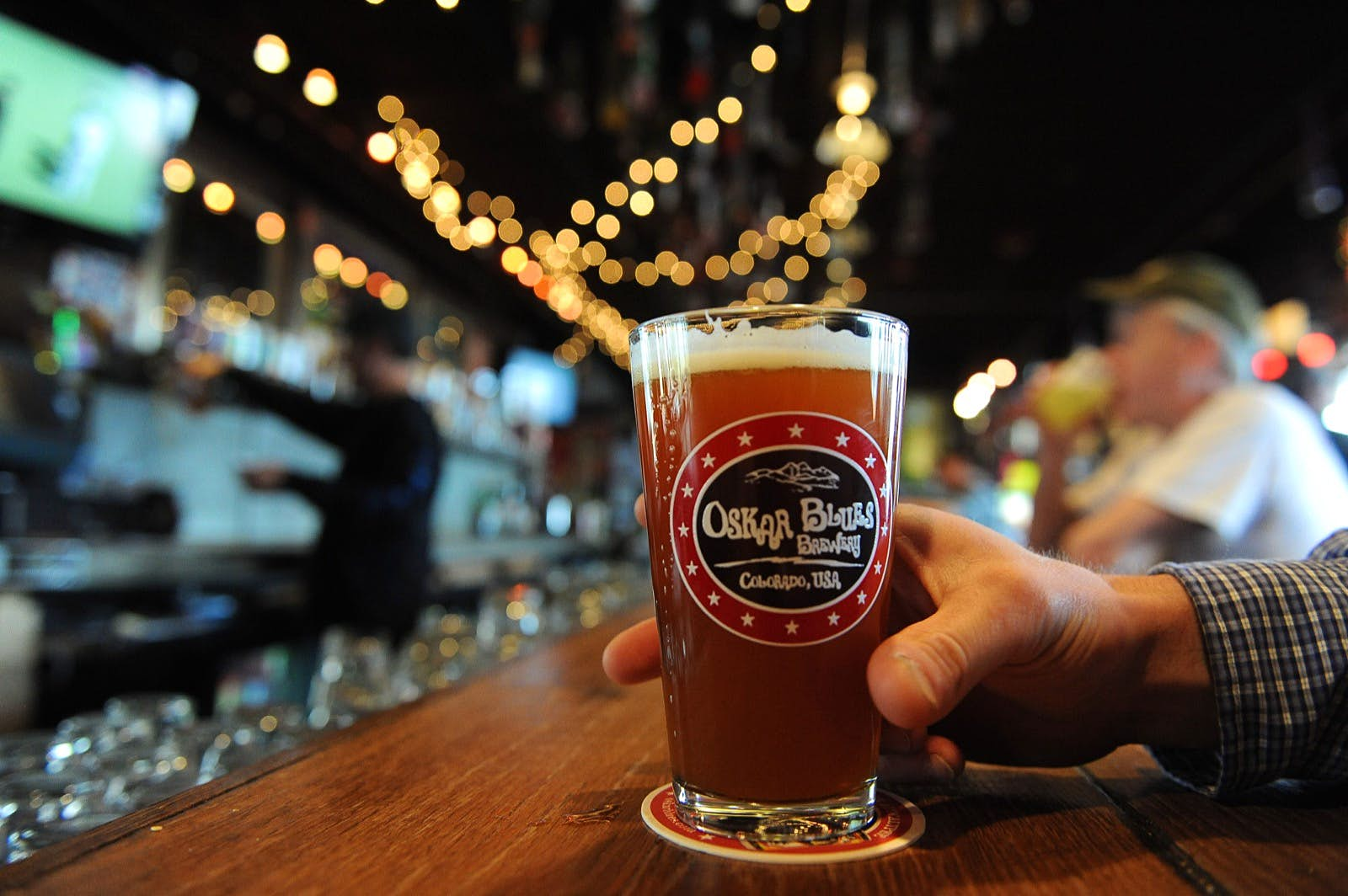 A man holds a glass of amber-colored beer resting on a circular coaster on a wooden bar. A collection of patrons drinking beer can be seen in the background. Oskar Blues is among one of the top craft breweries in the country.